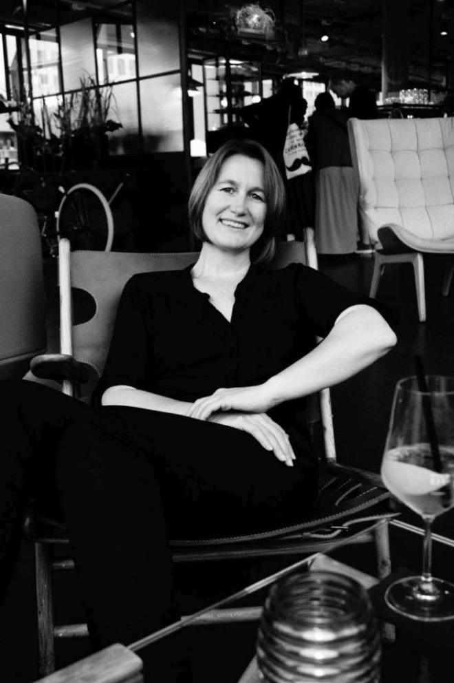 Yvonne Griesel, entspannt lächelnd in einem Restaurantstuhl mit Glas auf einem Tisch vor sich